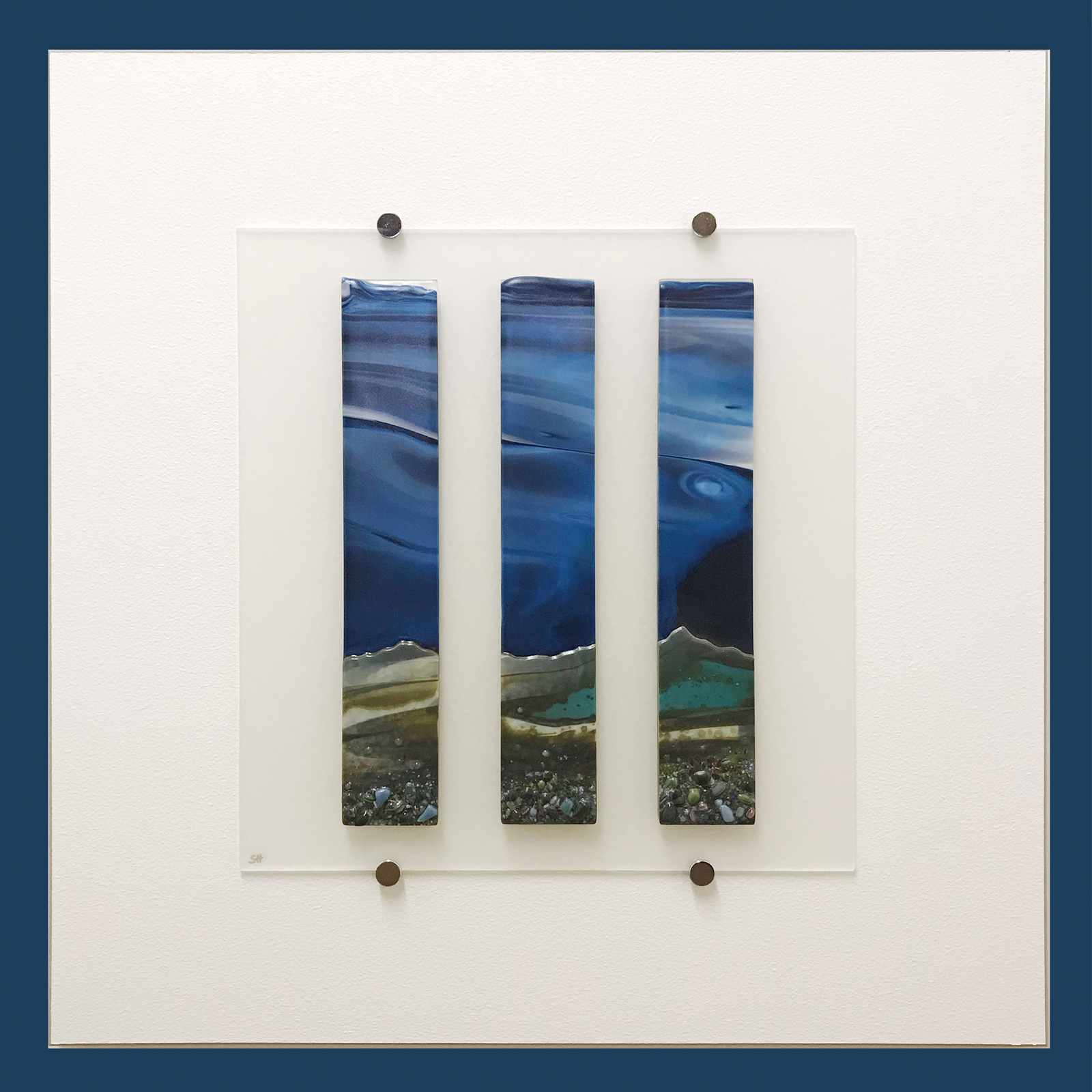 Glass Wall Art, coastal landscape triptych with moody blue sky clouds art, landscape greens and cream with glass frits in foreground.