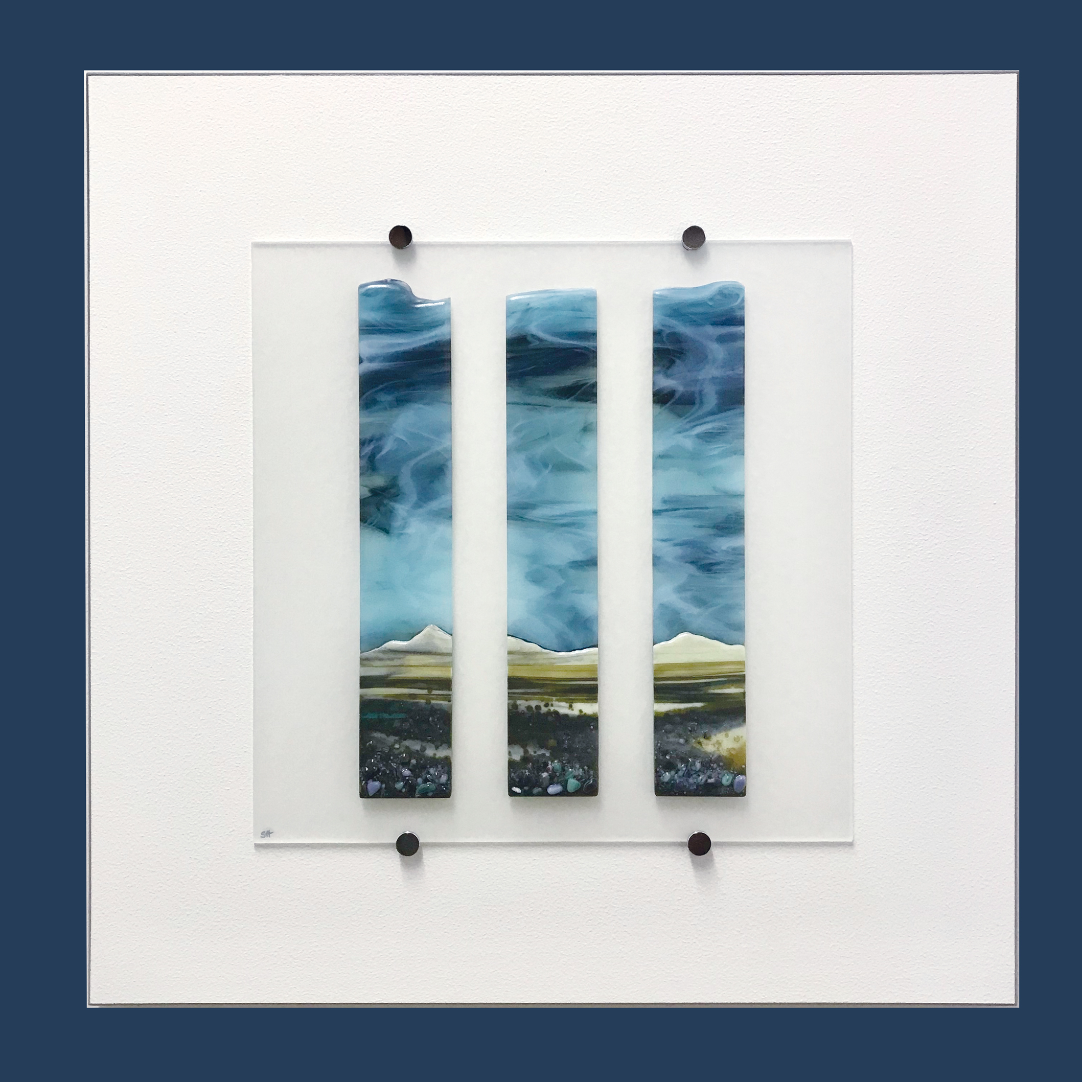 Glass Wall Art, coastal landscape triptych with moody blue sky clouds art, landscape greens/browns with glass frits in foreground.