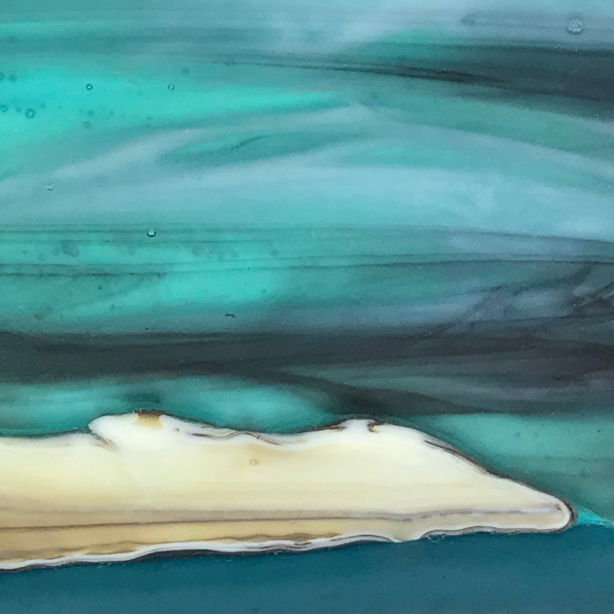Glass Wall Art, welsh seascape. Aquamarine sky with moody clouds. Steel blue sea. Headland, foreground with french vanilla/browns/teals glass frits to fore.Detail.