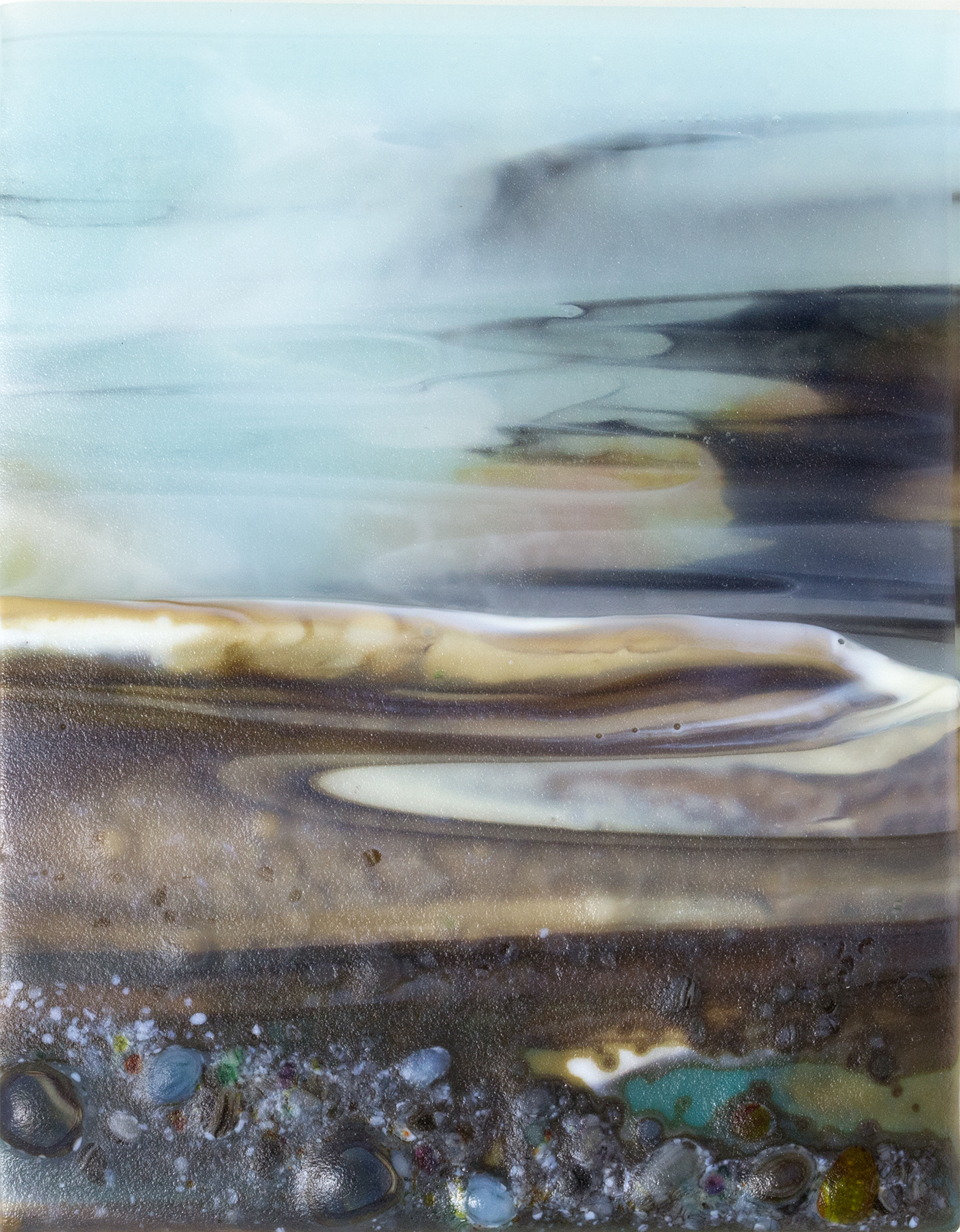 Glass Wall Art, landscape diptych with calm pale blue sky and low sunset, landscape teal/browns/vanilla headland with a mix of coloured glass frits in foreground.