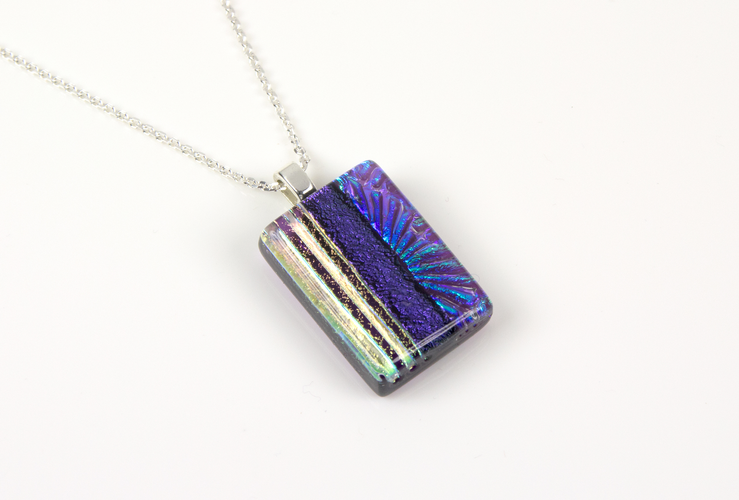 "Handmade glass pendant necklace with a clear violet base and a mix of subtle dichroic starburst and textured lines, divided by bold violet dichroic. Sterling silver 16-18"" chain."