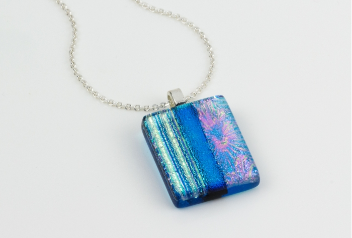 "Handmade glass pendant necklace with a clear turquoise base and a mix of subtle dichroic starburst and textured lines, divided by a bold pale blue. Sterling silver 16-18"" chain"