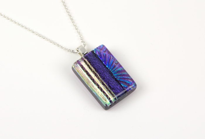 """Handmade glass pendant necklace with a clear violet base and a mix of subtle dichroic starburst and textured lines, divided by bold violet dichroic. Sterling silver 16-18"""" chain."""