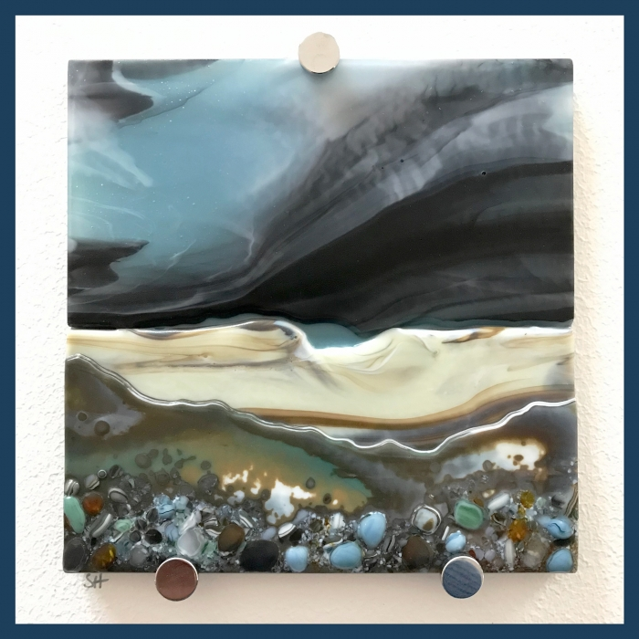 Glass Wall Art, coastal landscapes based on welsh landscape, with dark moody stormy sky clouds art, french vanilla and greens/grey with glass frits in foreground.