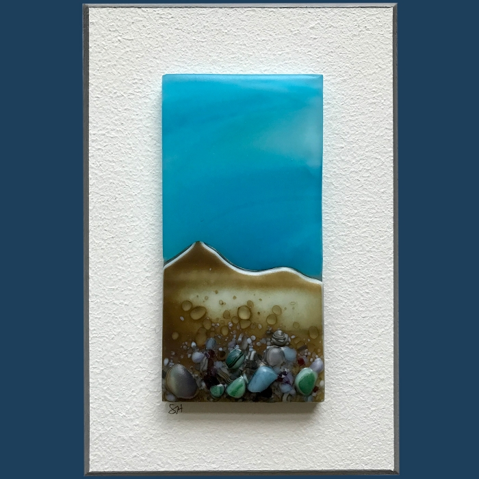 Seascapes fused glass wall art, welsh coastal landscapes, blue sky, vanilla/grey/green/brown/lilac glass frits in foreground.