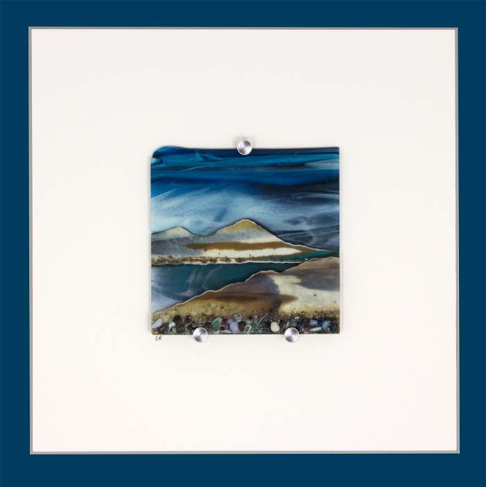 Glass Wall Art, welsh seascape.  Copper blue sky with wispy white clouds. Steel blue sea. Headland, foreground with french vanilla/browns/teals glass frits to fore.