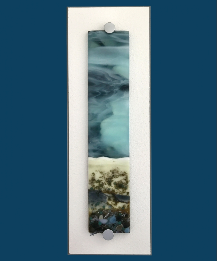 Winter Landscapes fused glass wall art – green/browns/vanilla/grey to fore, green/greys/brown specks, powder blue/grey sky. Satin finish.